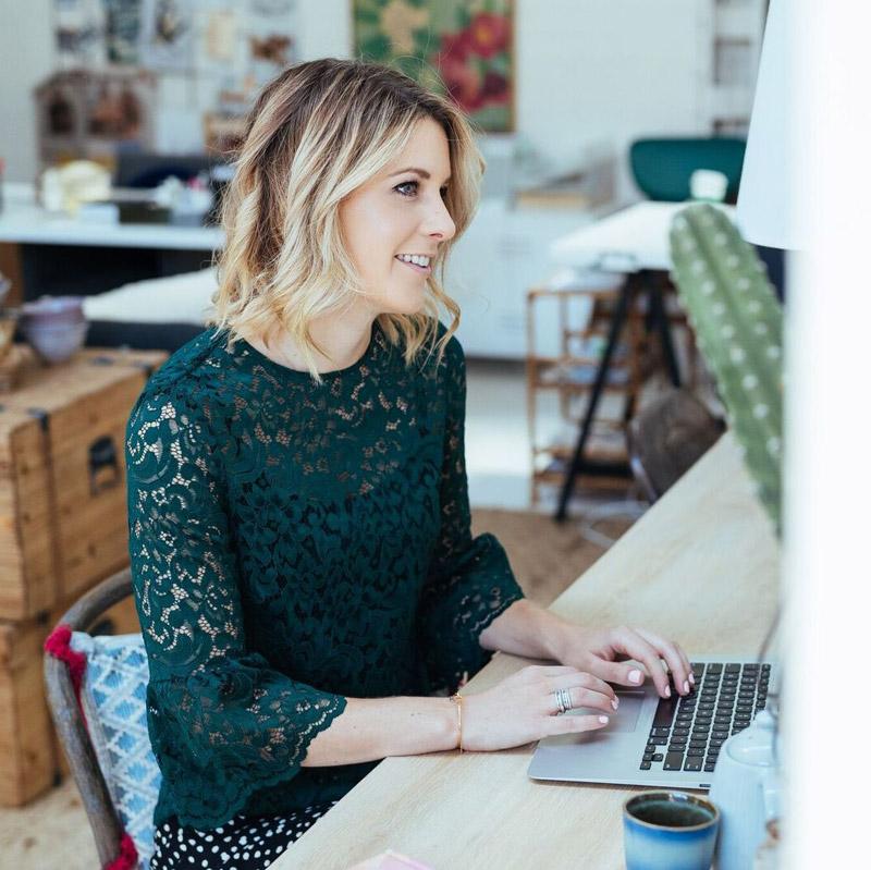 Emma Blomfield working at laptop in green dress